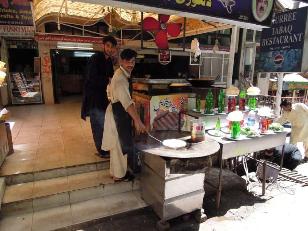 Two men smile as they make Paratha, a type of fried bread, in a Pakistani street stall