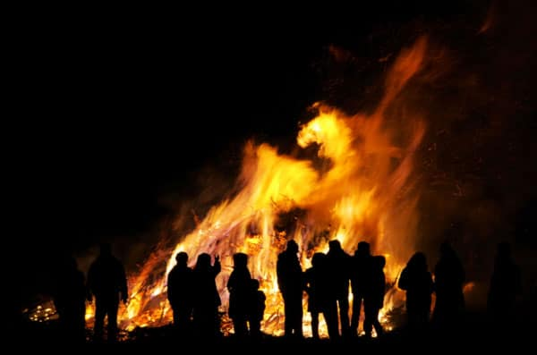 The silhouette of people celebrating can be seen in front of a huge bonfire on bonfire night